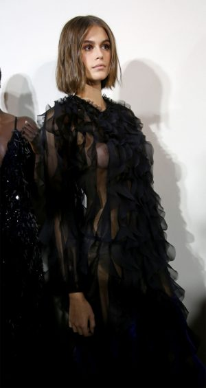 Kaia Gerber Braless Breasts in Black Lace Dress at a Fashion Show